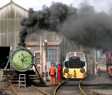 With a fresh round of 'best' coal on the fire just a little smoke was produced.... A compressed air feed acted as a blower. To the right of the boiler are 6024 Chairman & Engineering Manager Steve Underhill and, in red boiler inspector John Glaze. April 17 2004