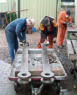Huw Button (left) and Steve Underhill work on the rear coupling rods. In the background Keith Clarke cleans one of the backhead fittings. May 08 2004 © Colin Henderson