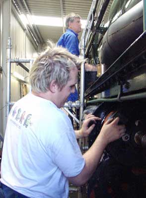 Having moved on from coaches Huw Button has graduated to preparing parts of the loco for painting. Here he rubs down the cylinder cladding. Above him Graham Hopes prepares the boiler for what is expected to be the final top coat. August 15 2004