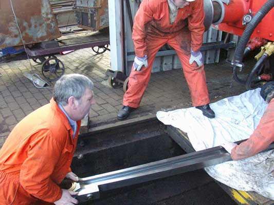 Keith Lines (left), Leon Salter (middle) and Mick Carr move the inside left connecting rod prior to refitting. February 07 2004