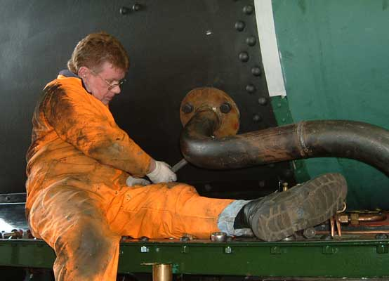 Kevin Blake helps tighten the bolts securing the outside steampipe to the smokebox. July 25 2004. © Colin Henderson