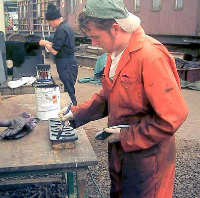 Leon Salter paints the smokebox numberplate whilst in the background Chris Brown paints some cladding pieces. May 15 2004 © John Salter
