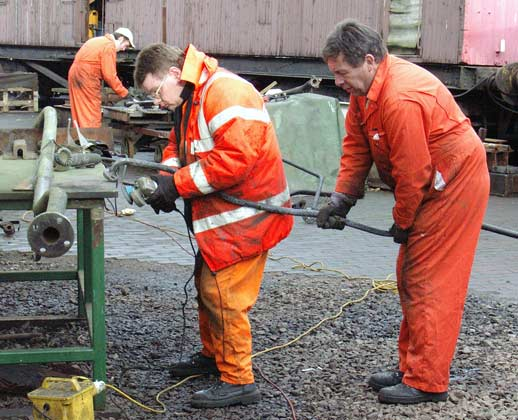 John Salter holds a piece of brake pipe whilst Kevin Blake wire brushes it. In the background Leon Salter is also working on some brake pipe work. January 10 2004