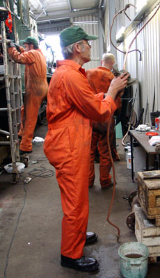 Pete Archer cleans up a freshly annealed copper pipe. Behind him Steve Underhill anneals another. June 19 2004