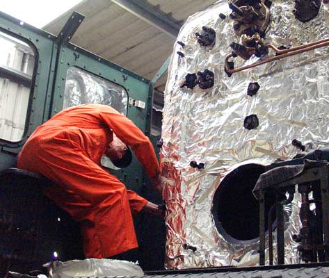Pete Archer applies the foil insulation and water protection layer the fireman's side of the firebox. May 29 2004