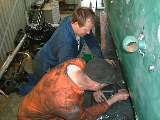 Steve Underhill (in the foreground) and Huw Button refit cladding around the firebox. June 26 2004 © Colin Henderson
