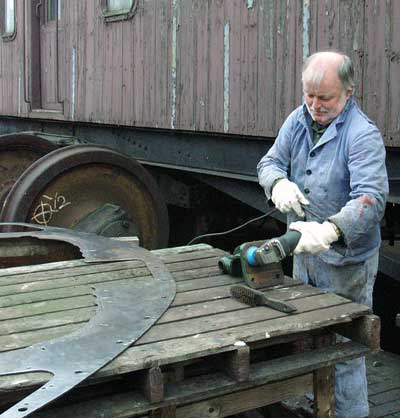 Brian Dodd cleans up a handrail bracket. On the left is the locomotives spectacle plate. November 9 2003