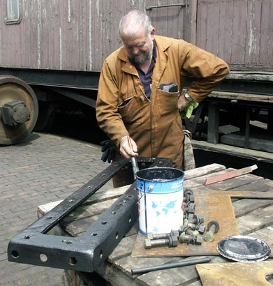 Colin Henderson paints the item that fits behind the front buffer beam to support the running plate. Once dry this was refitted. June 14 2003