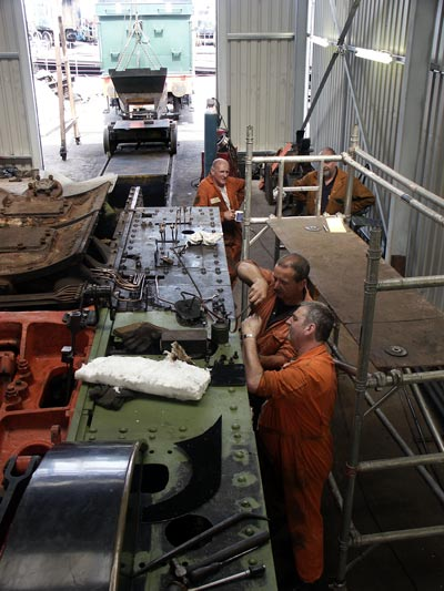 Keith Lines and Paul Sanders work on the cylinder. As can be seen the mechanical lubricator has been removed to allow the running plate to be repaired. Some sections have already been given a coat of paint. June 14 2003