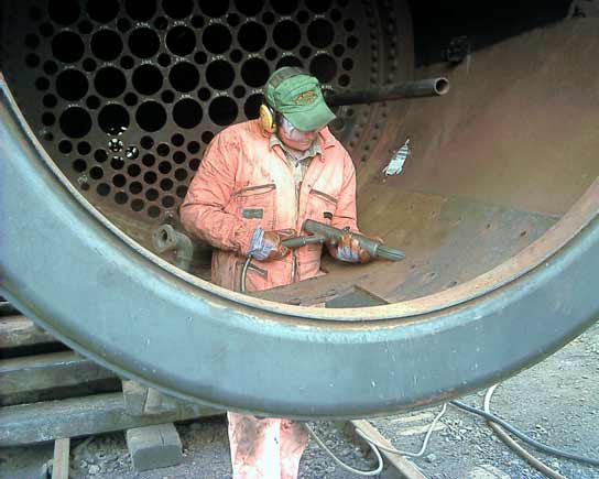 Leon Salter busy needle gunning the inside of the smokebox. June 14 2003 © John Salter