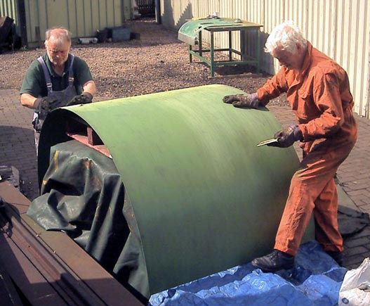 Brian Dodd (left) and Bob Robson rub down a primed cladding sheet before giving it a second coat. July 27 2003. © John Salter