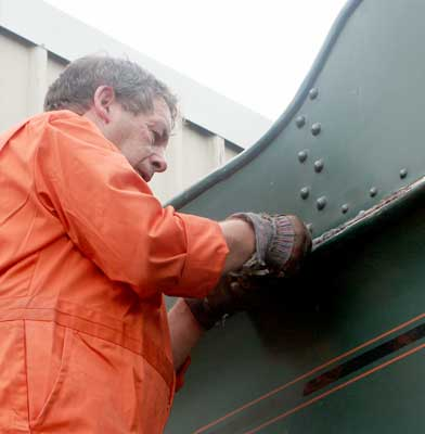 John Salter applies some anti-rust treatment to the tender. September 20 2003