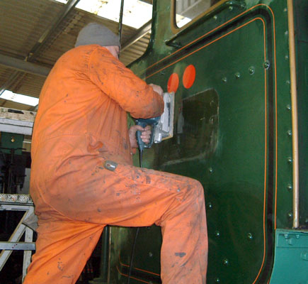 Mick Carr rubs down the drivers side cab sheet. January 31 2004 © Colin Henderson.