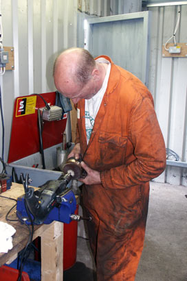 Steve Underhill works on one of the gland packing brasses. This one fits on the left hand outside piston rod. July 27 2003
