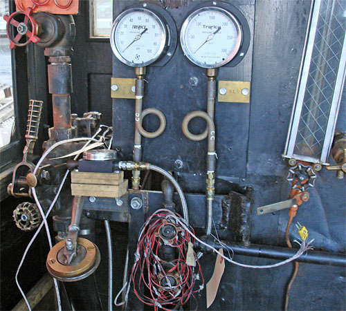This is what the fireman sees. Towards the bottom left is the fuel flow control valve. Above this are the gauges showing the atomising steam pressure and blower pipe pressure. The atomising steam control valve is located above the gauge, out of view in this image. This photograph was taken during the early days of testing hence the coil of cables and the gauge sat on wooden blocks above the fuel flow valve. © Nigel Day