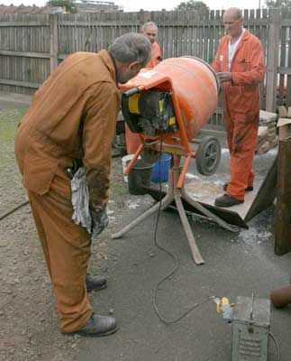 Colin Henderson struggles with the cement mixer controls as Steve Underhill and Keith Clarke put the materials in to be mixed. September 04 2004. © Huw Button