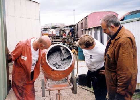 Hmm... What's in there then. Steve Underhill (left), Huw Button and Colin Henderson study the cement in the mixer. September 04 2004. © Keith Clarke