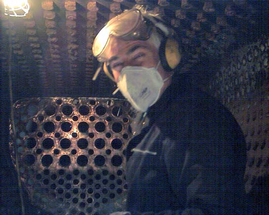 Chris Brown breaks off from needle gunning the crown stay nuts for a quick photo. Clear here is the copper firebox tubeplate March 8 2003 © John Salter