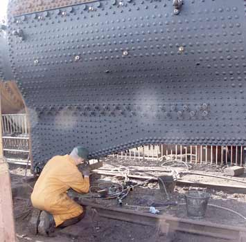 Colin Jeffrey, as close to the footplate as it is currently possible to get, works on the studs for mounting the ashpan to the firebox. March 23 2003. © Martyn Bane