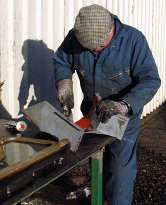 Keith Hudson fills some holes in on the the outside cylinder exhaust passage cladding pieces. December 21 2003