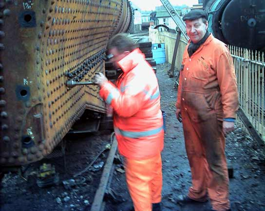 I don't think Dave Fuzard can quite believe how fast Kevin Blake is working. In something of a blur Kev cleans up the threads of the studs used to mount the firebox slides. March 8 2003 © John Salter