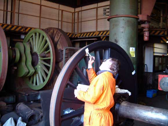 Kevin Blake paints white marks across the back of the tyre and wheel to enable us to detect any future tyre slip once the loco is back in service. March 16 2003. © Colin Henderson