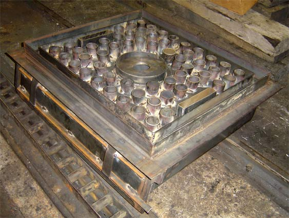 The panplate. This view shows the topside with the hole for mounting the burner prominent in the centre. The two slots are provided to allow the atomising steam superheater elements to be fitted. In due course the space between the air pipes etc was filled with fireclay. © Nigel Day