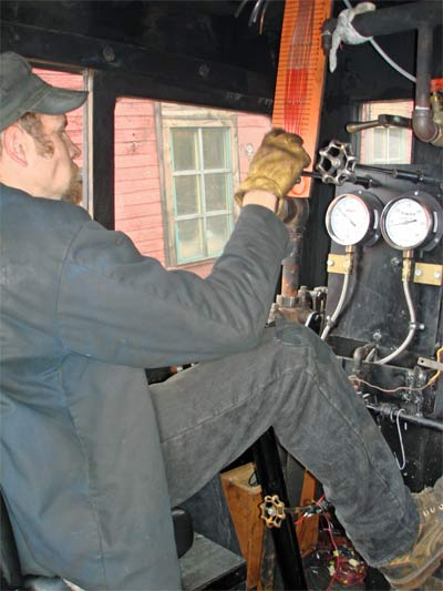 Fireman Mark Sodergren adjusts the atomising steam during testing. Note the manometer in front of him measuring vacuum levels at various points on the locomotive. © Nigel Day