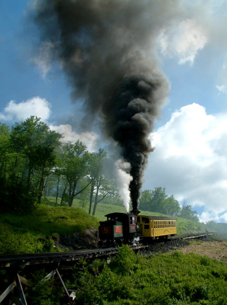A look back to 2004. A typical train on the Mount Washington Cog Railway starts away for the summit producing a column of smoke. All unmodified locos ascend the mountain emitting vast clouds of smoke. Money up the chimney in no uncertain way! © Nigel Day