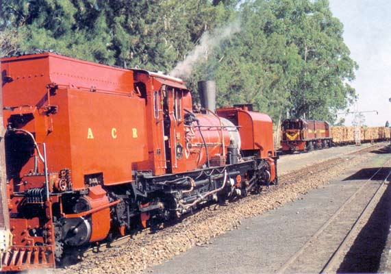 'NGG16a' No 141, seen in its striking red livery on the Alfred County Railway. At the head of the 'Banana Express', the Garratt is waiting to pass a double-heading pair of Class 91 diesels with the ACR's life-blood - a timber train from Harding. © A.A. Jorgensen